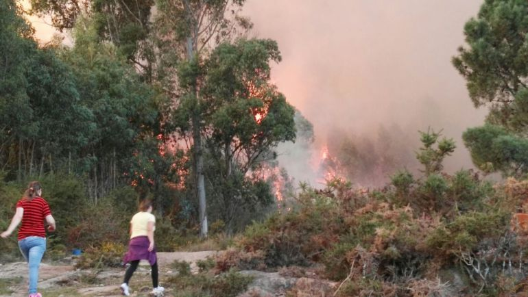 Dos vecinas corren cerca de donde están las llamas del incendio declarado en Mondariz