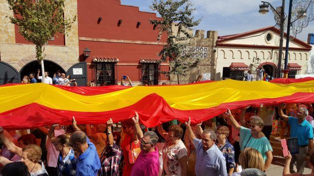 Los vecinos y muchos visitantes han participado en el acto para desplegar la bandera española