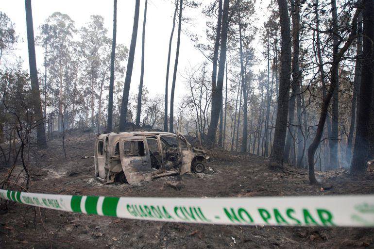 El coche donde fallecieron dos mujeres, víctimas del fuego, en la zona de Chandebrito en Nigrán (Pontevedra). Las altas temperaturas y los fuertes vientos han magnificado el efecto de los incendios en las Rías Bajas, que estos días presentan unas temperaturas veraniegas