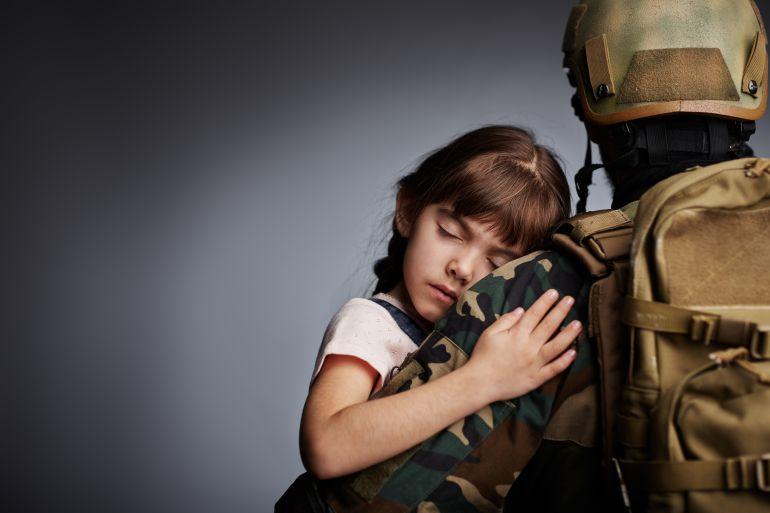 Niña durmiendo en brazos de un militar