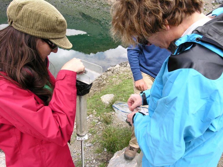 Las investigadoras extraen  un testigo de sedimento en una de las lagunas de Sierra Nevada