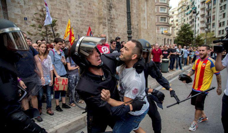 Agentes de la policía tratan de controlar a un joven durante la tradicional manifestación de entidades de izquierda y nacionalista del 9 d'Octubre