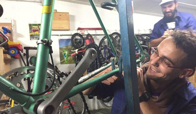 Antonio reparando una bicicleta en el taller.
