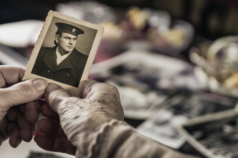 Imagen de una anciana mirando fotos antiguas