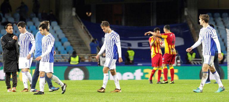 Los jugadores de la Real se retiran cabizbajos mientras el Lleida celebra su clasificación