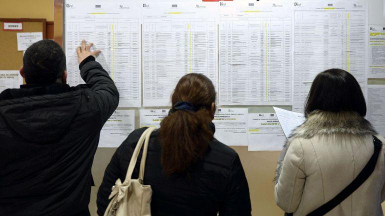 Personas consultando listas del paro.