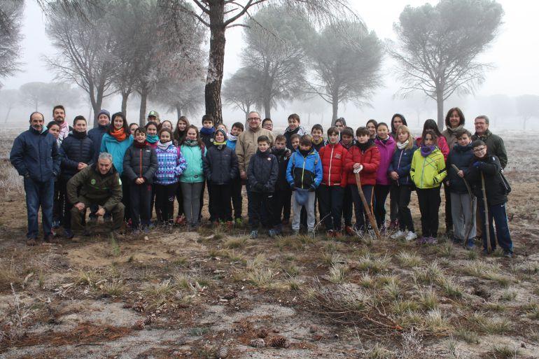 El delegado territorial junto a los alumnos del instituto de Nava tras la plantación de pinos en los montes afectados por el incendio