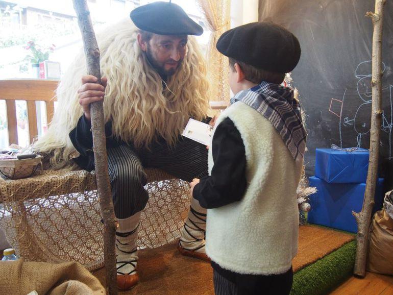 Un niño entrega la carta con la lista de regalos a Olentzero