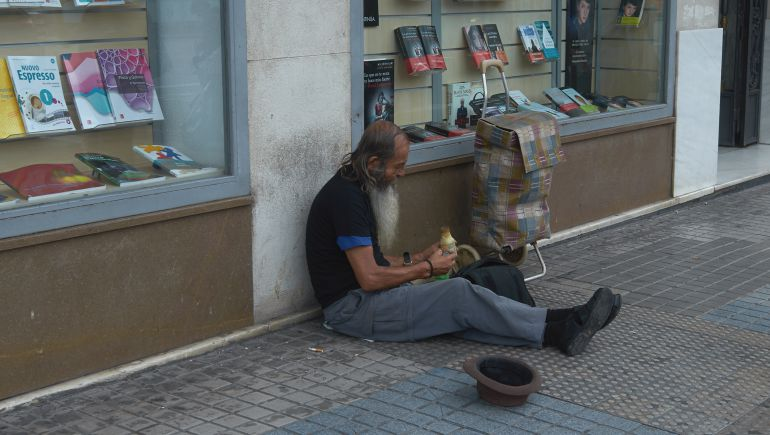 Persona pidiendo limosna en una calle del centro de Valencia