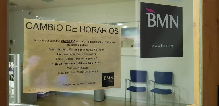 Las oficinas de BMN en localidades pequeñas, como esta de Válor (Granada), comenzaron en 2017 a reducir su horario de atención al público, como muestra el cartel