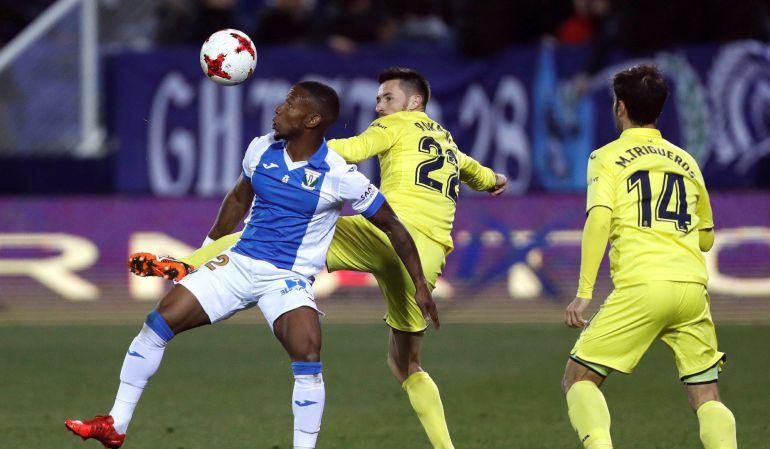 El delantero del Leganés, Beauvue (i), lucha por el balón ante el defensa del Villarreal, Rukavina (c) y el centrocampista, M. Trigueros (d), durante el partido de Ida de los octavos de la Copa del Rey de fútbol, disputado en el estadio de Butarque, en Leganés.