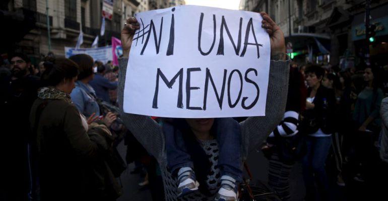Una mujer lleva una pancarta en contra de la violencia de género durante una manifestación.