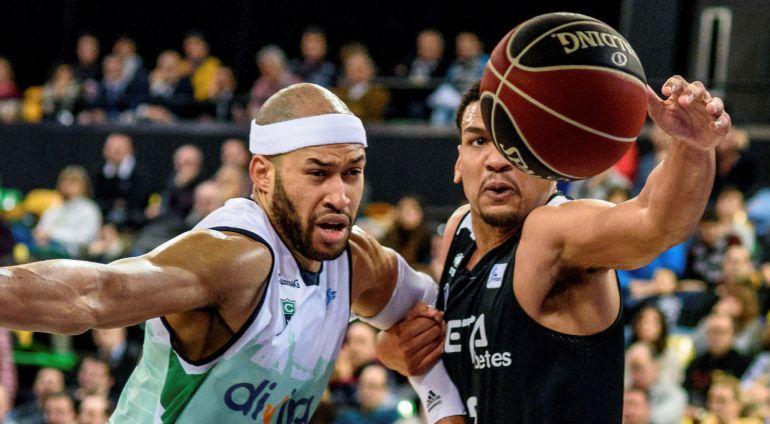 El alero estadounidense del Bilbao Basket Devin Thomas (d) lucha un balón con el pívot jamaicano del Joventut Jerome Jordan (i) durante el partido de la decimosexta jornada de Liga ACB disputado hoy en el Bilbao Arena
