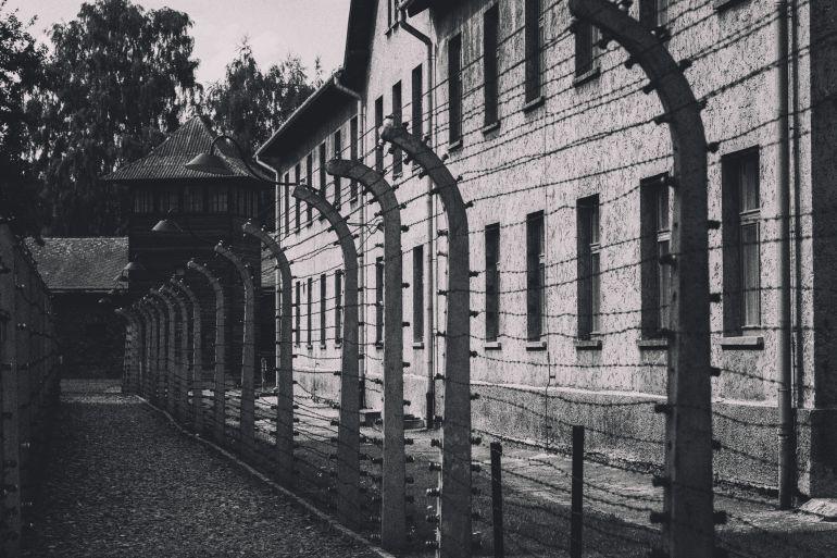Valla de alambre de púas en Auschwitz  Oswiecim, Polonia - 16 de agosto de 2016: Una cerca del alambre de púas y en el fondo una guardia. El sitio es el campamento original (Auschwitz I) del campo de concentración de Auschwitz, ahora el Museo Estatal Auschwitz-Birkenau.