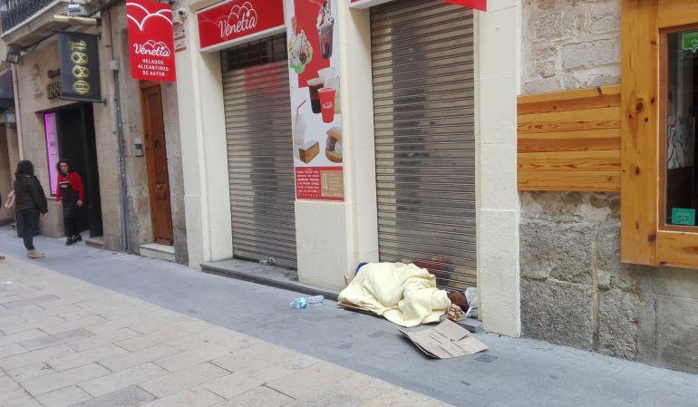 Una persona sin hogar duerme cobijado en un establecimiento en pleno centro de Alicante.