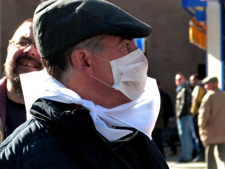 Un hombre durante la manifestación con una mascarilla en la cara.