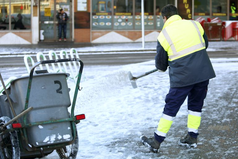 Un operario esparce sal en una calzada con nieve y hielo