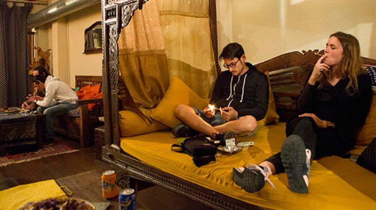 Dos jóvenes consumiendo marihuana en un club de cannabis.