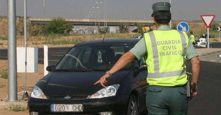 Un agente de la Guardia Civil ordena parar a un vehículo en una carretera.