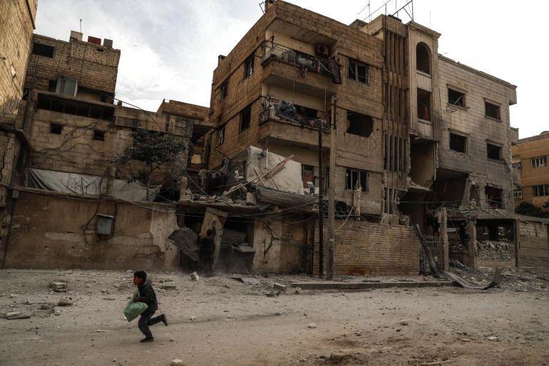 Un niño corre junto a edificios derruidos después de un bombardeo en Duma, Guta Oriental (Siria)