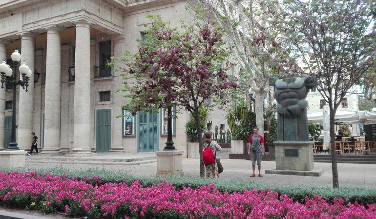 Unos turistas se fotografían a las puertas del Teatro Principal de Alicante.