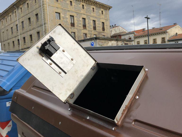 Tapa con la apertura lateral en uno de los contenedores marrones.