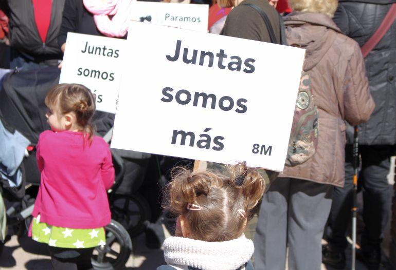 Dos niñas portan pancartas alusivas a la huelga con motivo del Día de la Mujer