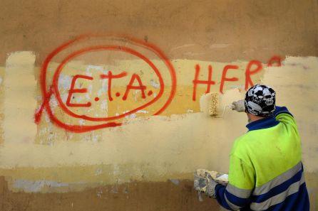 """Un trabajador municipal pinta sobre el graffiti leyendo """"ETA, El pueblo está contigo"""" en Gernika, un día después de que el grupo separatista vasco ETA anunciara un cese definitivo de la actividad armada."""