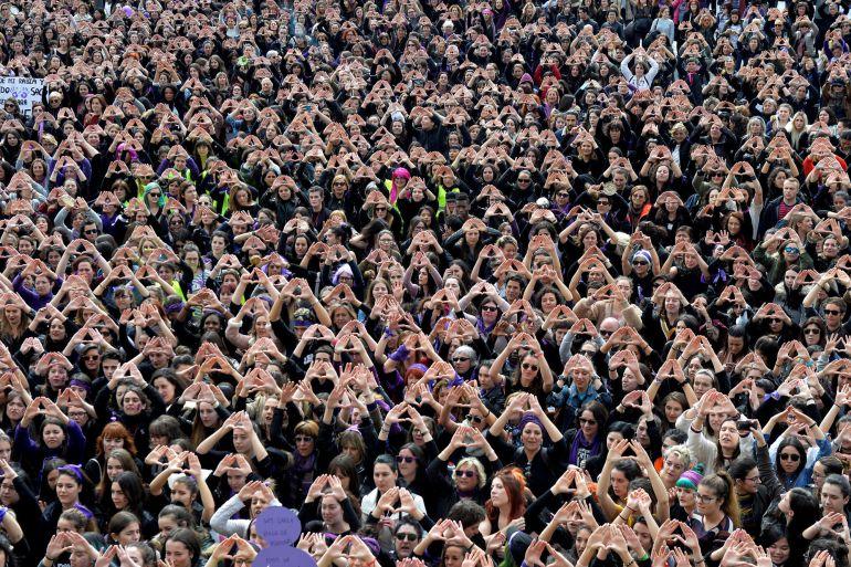 Los manifestantes forman triángulos con sus manos durante una manifestación por los derechos de las mujeres en Bilbao, el 8 de marzo de 2018, en el Día Internacional de la Mujer