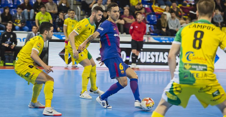 Varios jugadores del Jaén FS intentan frenar el avance de un hombre del Barcelona FS.