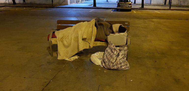 Una persona sin hogar pasa la noche frente a la estación de autobuses de Granada