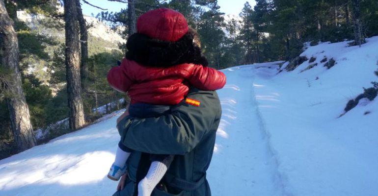 Un agente de la Guardia Civil con uno de los menores rescatados en brazos.