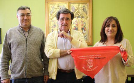 La concejal de Turismo muestra un pañuelo rojo con la palabra 'Internacional' escrita a mano. Acompañada del alcalde de Cuéllar y el concejal de Festejos