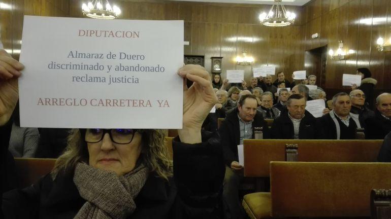 Una vecina de Almaraz muestra un mensaje a favor de la carretera en el Pleno de la Diputación de diciembre de 2017