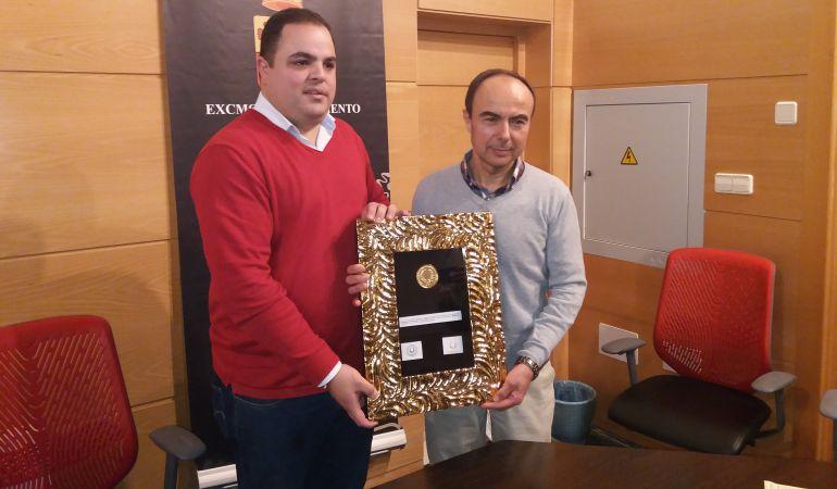 José Domínguez mostrando su galardón junto al alcalde de Martos, Víctor Torres