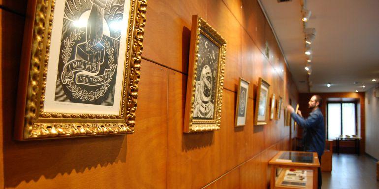 Telmo Iridoy, al fondo, colocando cuadros que forman parte de su exposición en el Gazteleku.