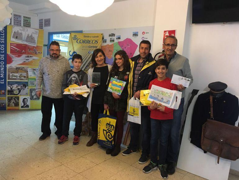 Juan González posa con los sellos conmemorativos de Nigrán y alumnos del Carlos Casares participantes en el concurso