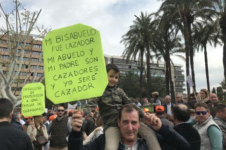 Un abuelo y su nieto portan una pancarta durante la concentración.