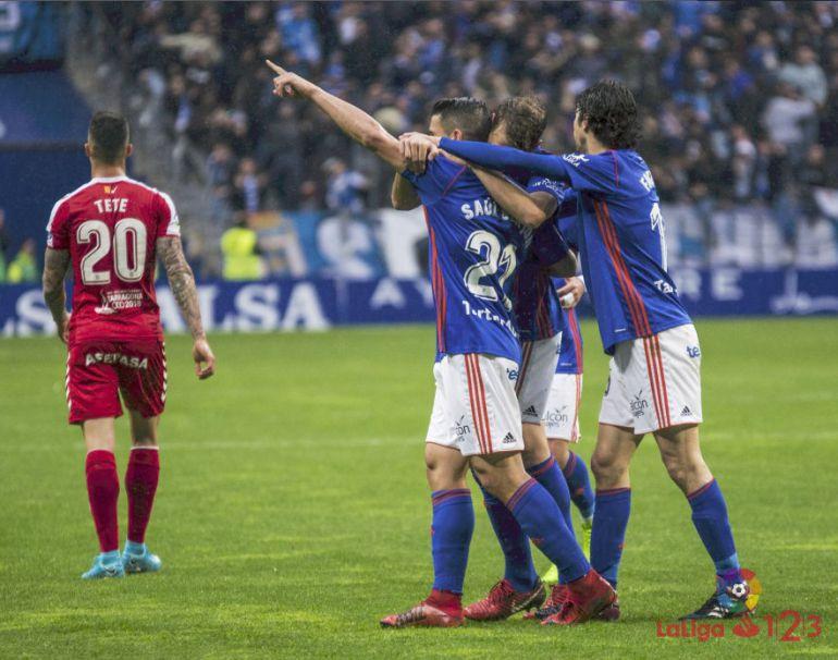 Saúl Berjón señala a la grada tras marcar el gol mientras es abrazado por sus compañeros.
