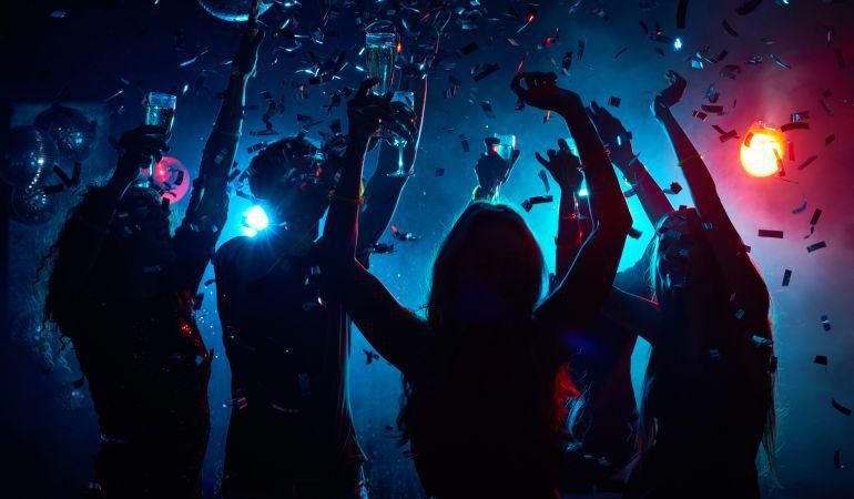 Cinco jóvenes bailan en una discoteca.