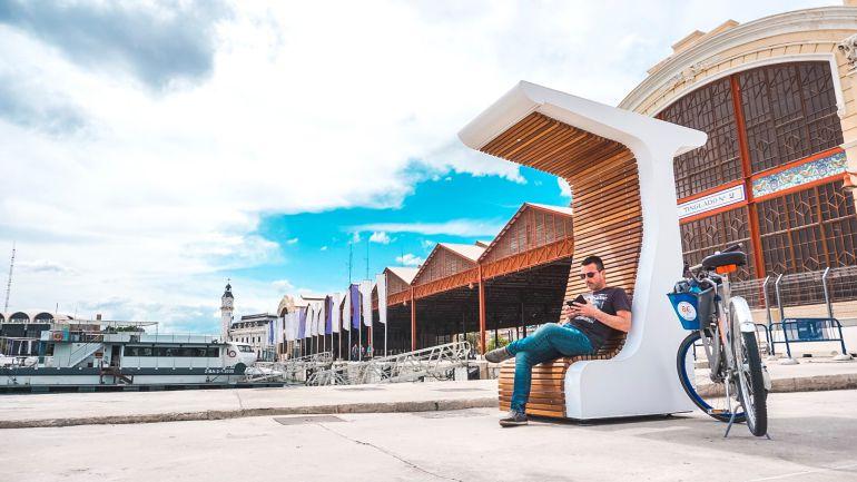 Un banco solar que permite conectarse a Internet por Wifi, cargar por inducción dispositivos electrónicos móviles y acceder mediante una pantalla táctil a apps de interés para turistas y ciudadanos