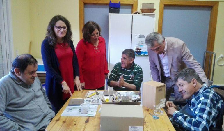La consellera Mónica Oltra (i), junto a la directora del Centro San Rafael, Ana Carratalá, (d) en la visita a uno de los talleres.