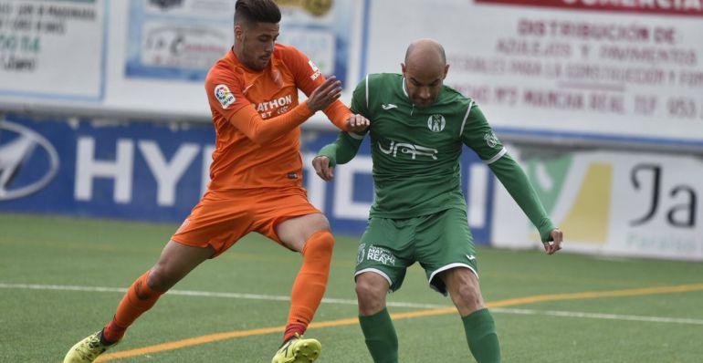 Óscar Quesada trata de mantener el balón ante la presión de un rival del Atlético Malagueño.