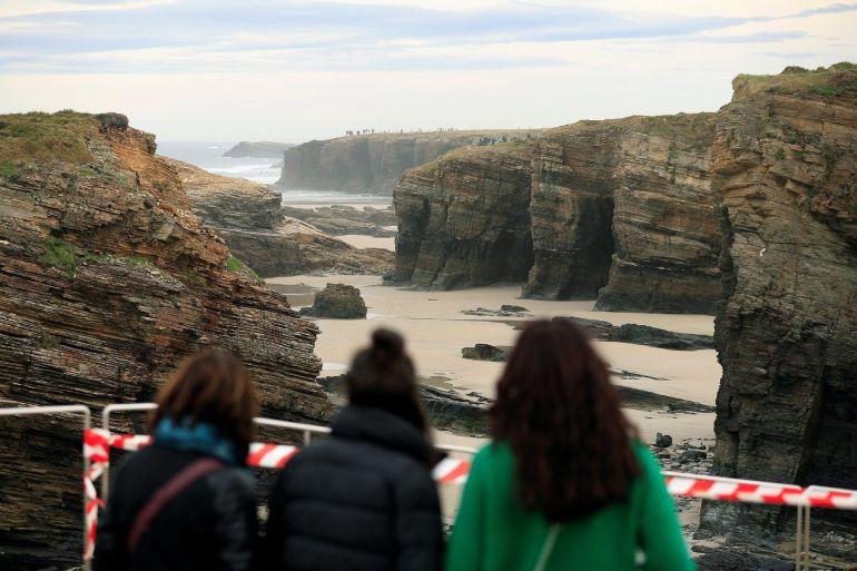Varias personas observan de lejos el arenal en el que falleció una joven el pasado mes de marzo
