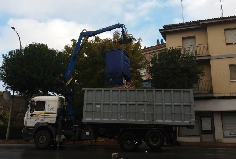 Operarios de una empresa de recogida de papel vacían uno de los contenedores en un camión.