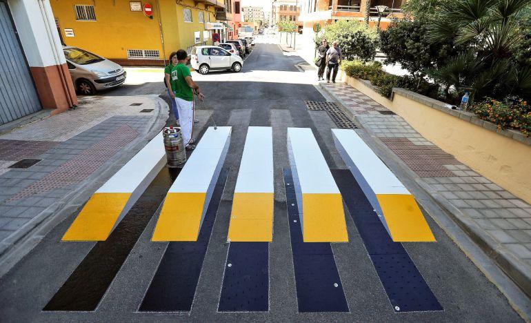 Un operario trabaja en la colocación del primer paso de peatones en 3D termofusible de España.