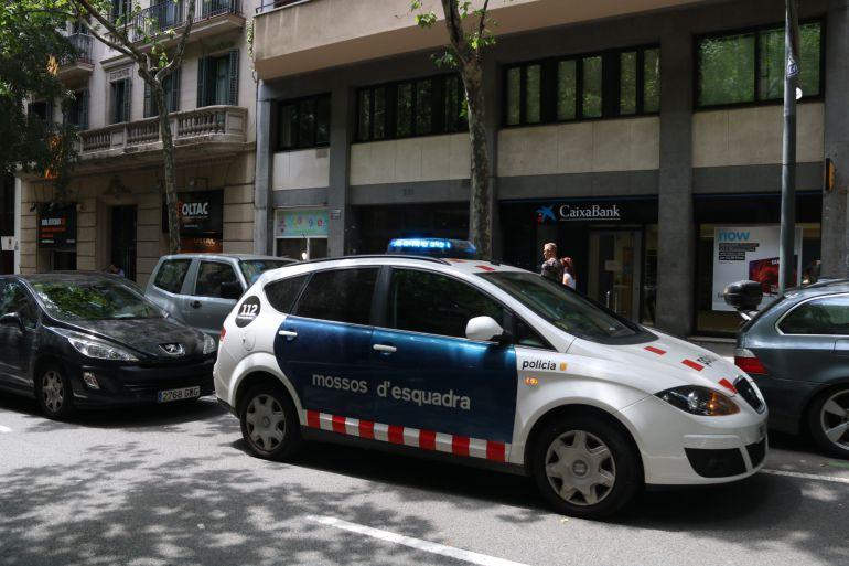 Una dotació dels Mossos d'Esquadra davant de l'entrada del bloc on han trobat el cadàver del nadó