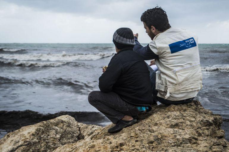 Un trabajador de Aldeas Infantiles habla con un menor frente al mar