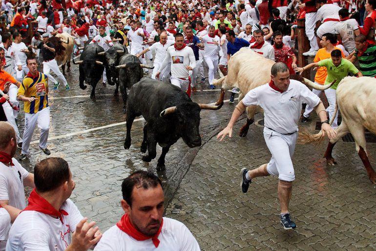 Mozos y toros en el tramo de Telefónica a punto de entrar en el callejón de la Plaza en el segundo encierro de los Sanfermines de 2018