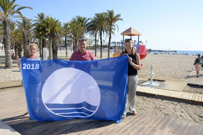 El alcalde José Chulvi y las concejales Doris Courcelles y Kika Mata, con la bandera azul del Arenal.